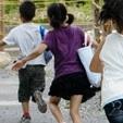 送迎バスを降り、校舎に向かって飛び跳ねるように走り出す子どもたち